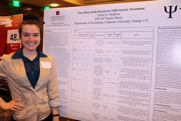 Student stands with research board