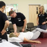 Members of the Department of Physical Therapy stretch out a patient.