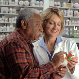 Pharmacist helps a patient with their prescription.