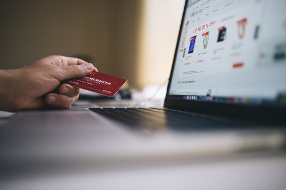 Picture of a laptop and a hand holding a credit card