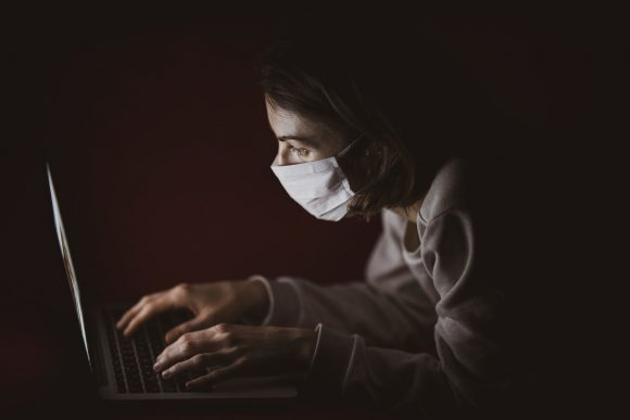 Woman typing on a laptop in the dark while wearing a mouth and nose mask