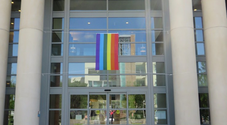 A rainbow pride flag hangs from the main entryway to the Leatherby Libraries.