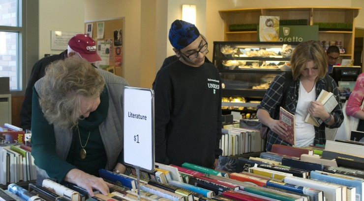 People searching through books for sale.