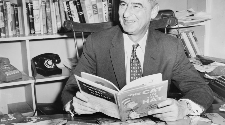 Author Dr. Seuss holding The Cat in the Hat and smiling.