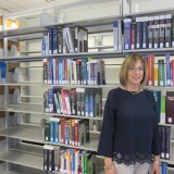 Woman standing next to books on shelf in library.