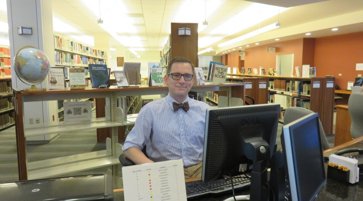 Man in bowtie using computer in library.