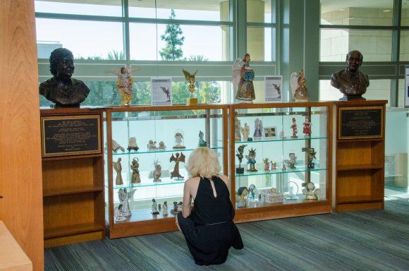 A woman kneels facing away from the camera, looking at a display case full of angel figurines