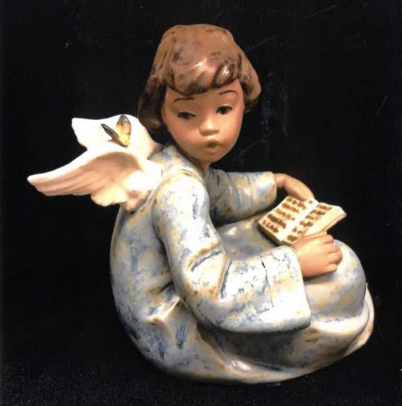 A small porcelain figurine of a seated angel reading a book,.