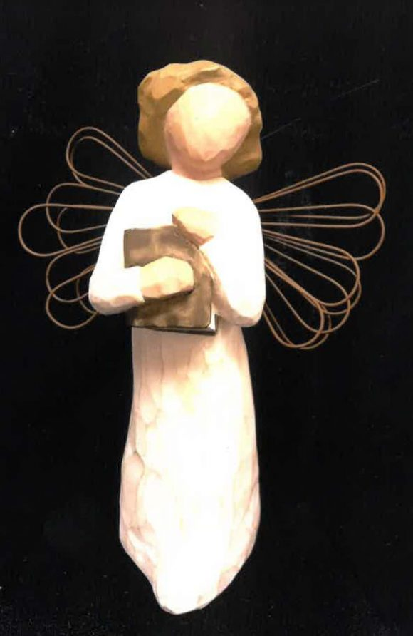 A small wooden figurine of a female angel with wire wings holding a book.