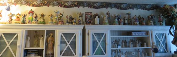 A variety of angel figurines lining the top of a cabinet.