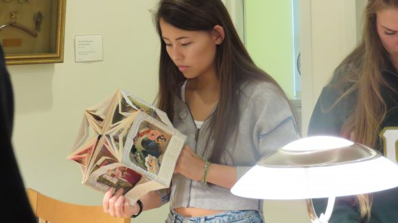 A female college student handles a carousel book.