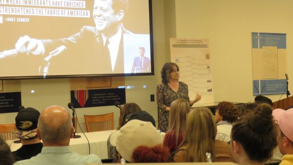 A woman stands in front of a seated crowd, giving a presentation. To her right is a projector screen featuring an image of John F. Kennedy.