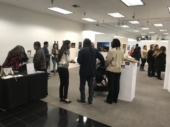 Photograph of a crowd of people viewing an art exhibit