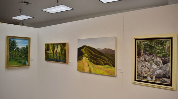 Photograph of four paintings hanging on a wall