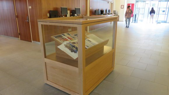 A display case in a library lobby, with books inside