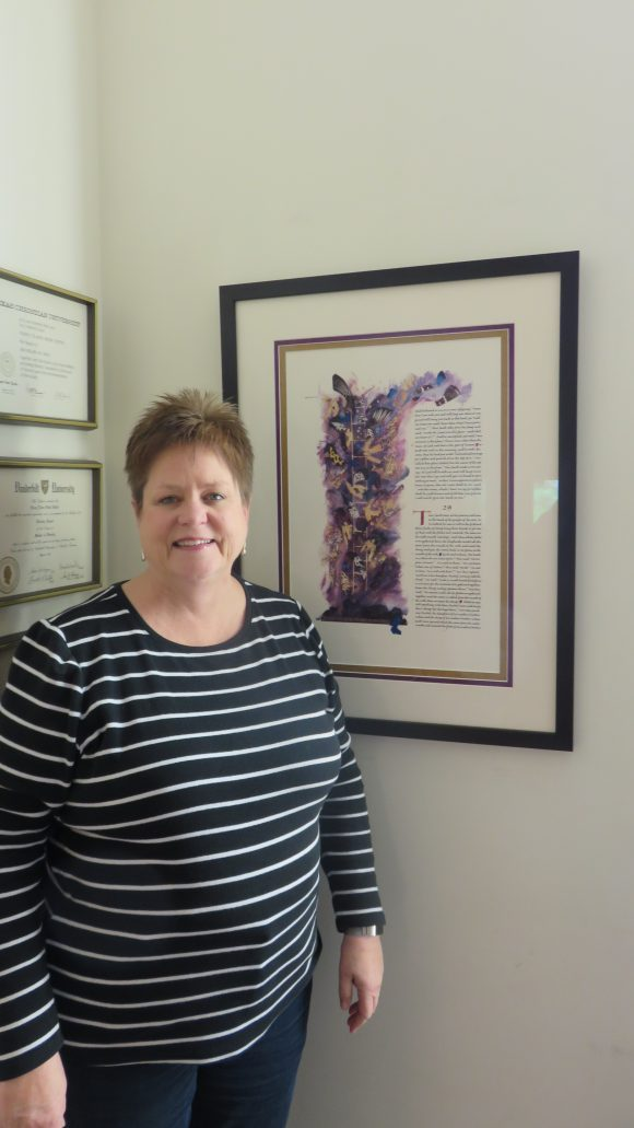 An adult woman stands next to a framed print hanging on a wall