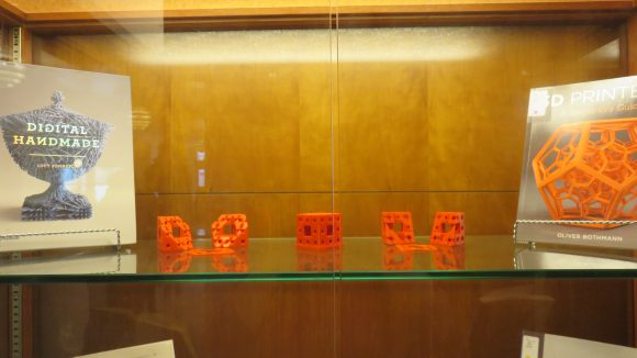 A shelf in a display case with two books on either side, and three small orange objects between the books