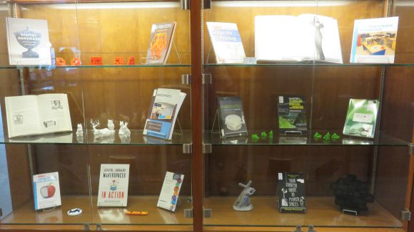 A display case with six glass shelves, each holding between one and three books and between two and six small 3D-printed objects