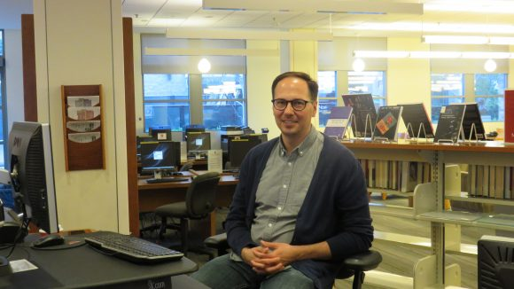 Male librarian sits at reference desk