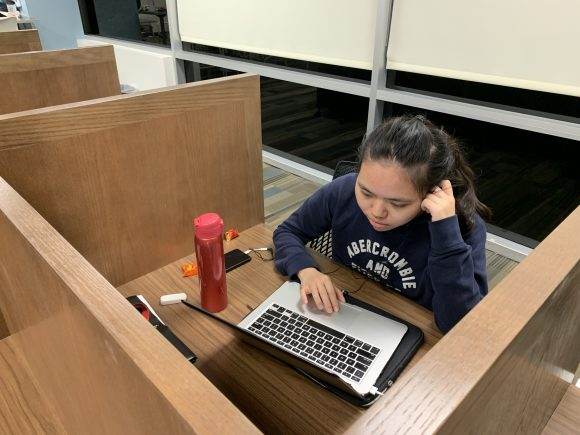 A young female student sits at a carrel, focusing on her laptop.