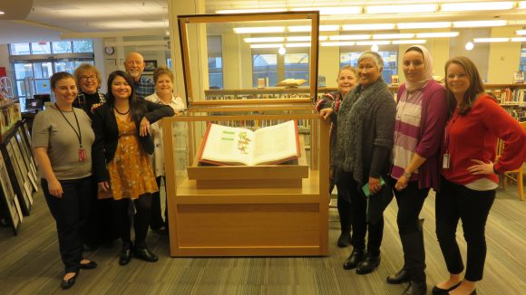 Group of faculty and staff stand around an open case with illustrated bible inside.