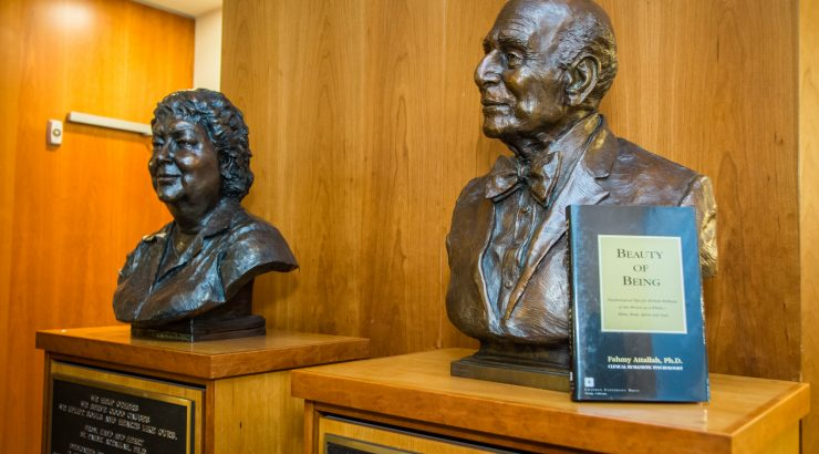 Two bust statues - one of a woman and one of a man - stand on wood platforms, with a book resting on the male bust.