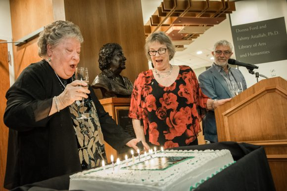 Woman holding a champagne class prepares to blow out the candles on a large birthday cake. Another woman stands in the middle, singing, and a man stands behind her looking on.