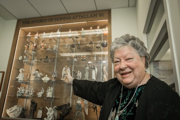 A woman on the right side of the frame points behind her to a display case filled with figurines.