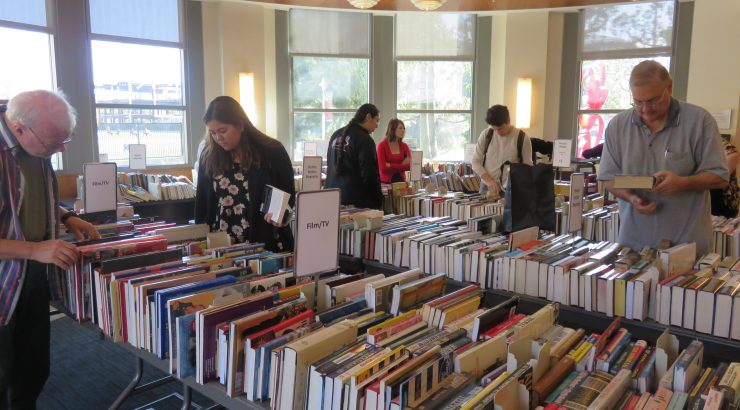 Several adults, some in the foreground and some in the back, look through tables of books, organized by genre.