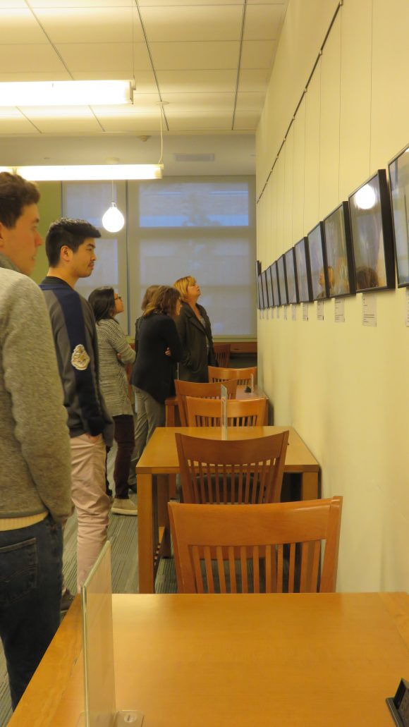 Group of students stand, looking at art hanging on the wall.