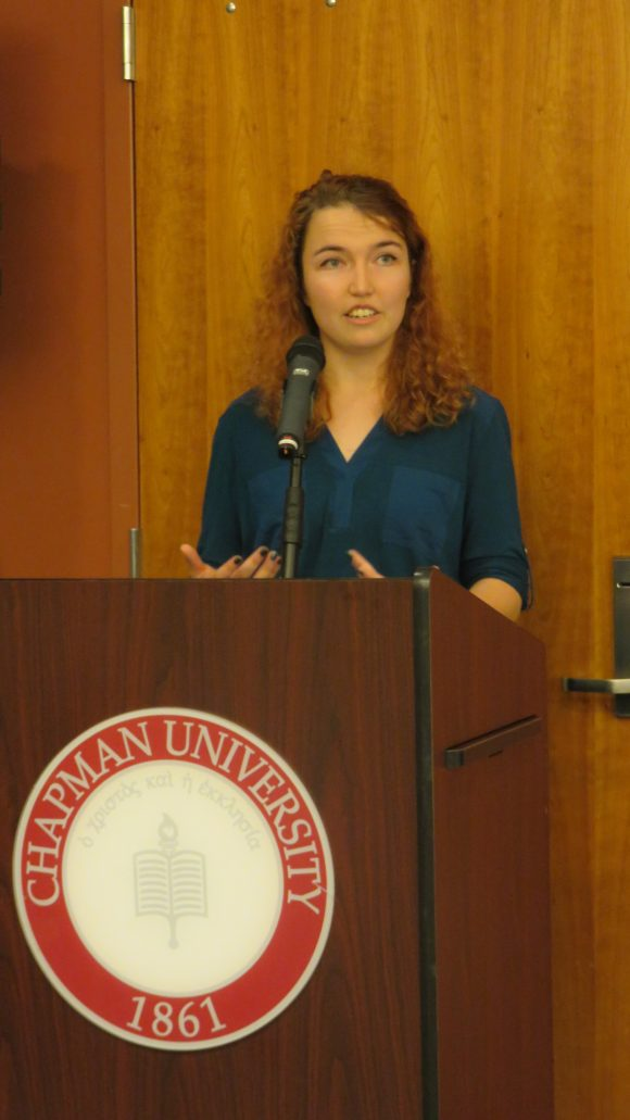 Young woman stands behind a podium talking.