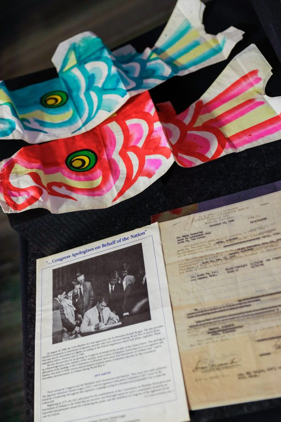 Two colorful paper kites decorated like fish sit on a table behind two archival documents.