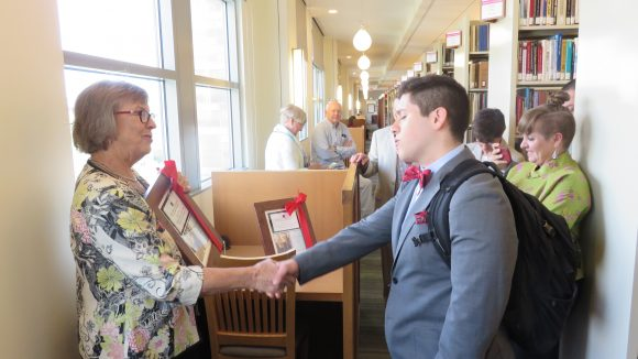 A woman on the left shakes the hand of a young male college student on the right, handing him a wrapped, framed photo, while people look on from the background.