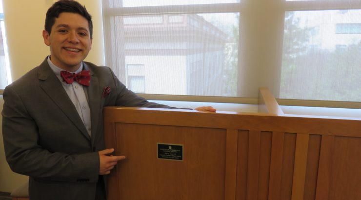 A young man stands next to a study carrel, pointing at the plaque on it that lists his name.