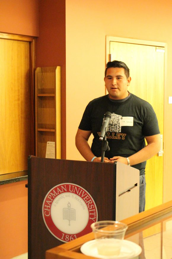 A young man in a t-shirt stands behind a microphone at a podium.