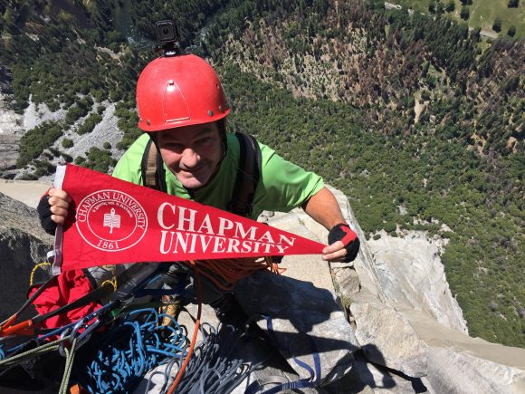 A man hangs from a cliff face, with a steep drop behind him. He is holding a red Chapman University pennant.