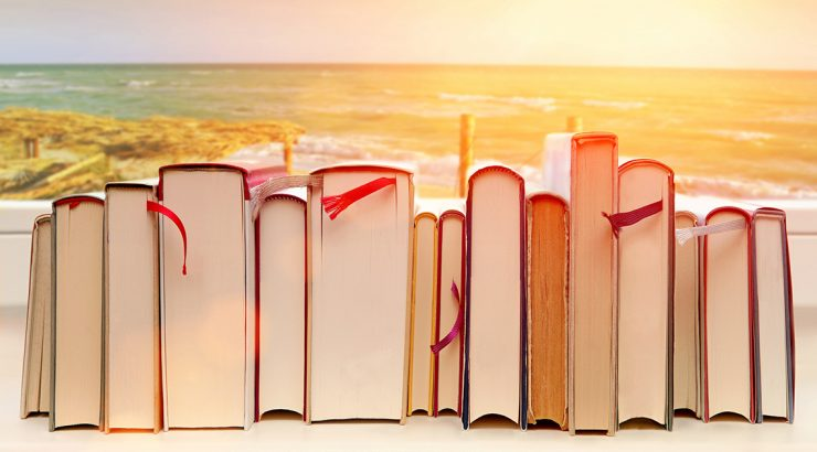 Graphic of the edge of a stack of books, horizontal, superimposed against a background of a sunset over a beach,