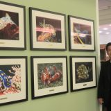A man stands to the right of the frame, posing next to six framed photos on the wall.