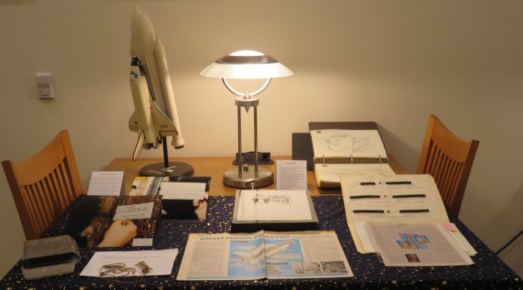 Multiple materials, some printed, some photographs, and one model of the Challenger shuttle, displayed on a table with a lamp in the background.