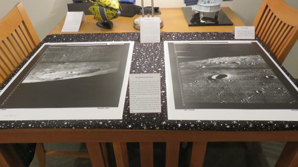 Two photographs of the moon's surface displayed on a wooden table over a moon and star patterned scarf