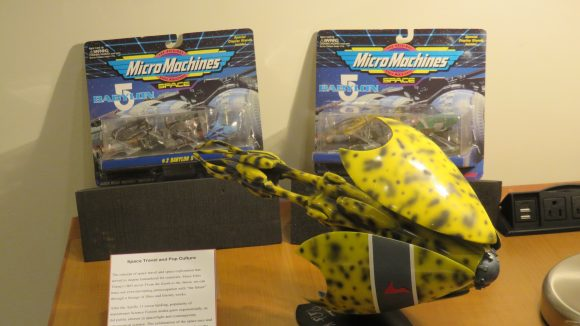 Three toys (two Micro Machines in wrapping in background, one yellow toy in foreground), displayed on a wooden table with explanatory text (included in this essay) next to them.