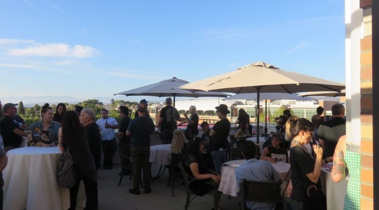 A crowd of people sit and stand on a patio, with a blue sky and mountains in the background.
