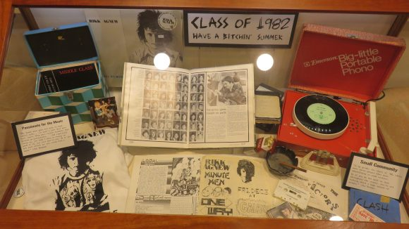 "Display case filled with material, titled, ""Class of 1982"""