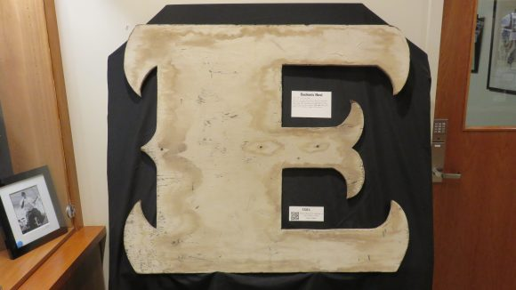 "A large plywood capital ""E,"" displayed on a black board."