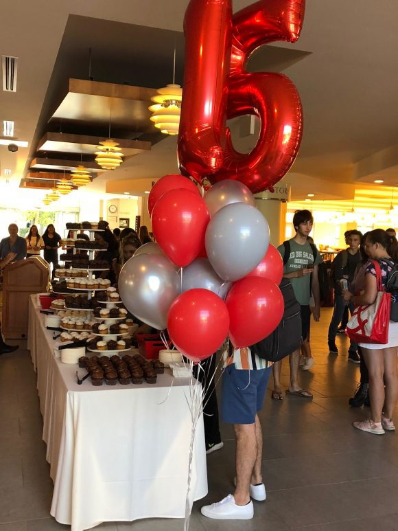 """A cluster of red and gray balloons, with two number balloons spelling out """"15,"""" stand in front of a table filled with cupcakes."""