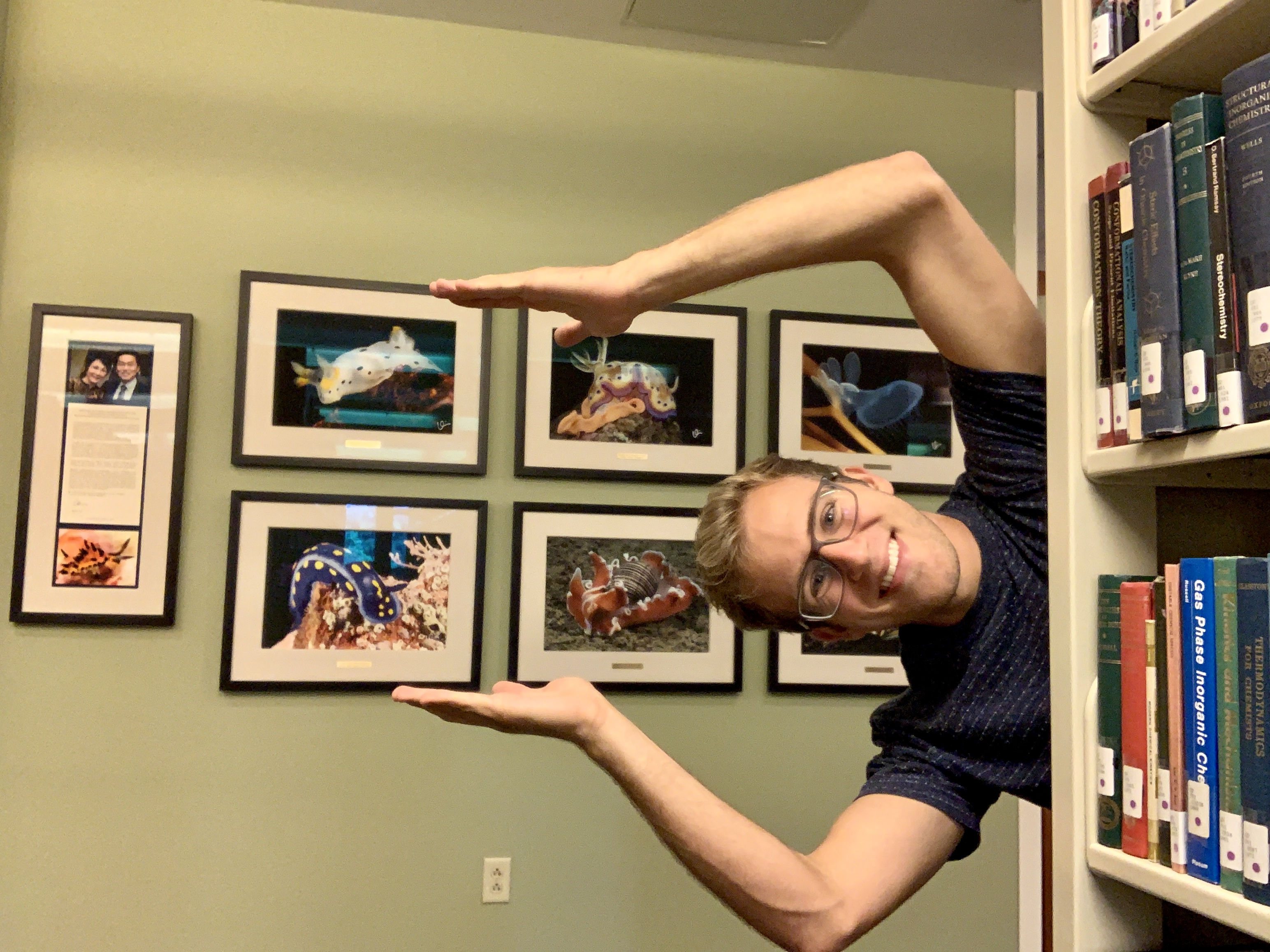 Jimmy posing sideways, as if swimming, with a wall of framed photos behind him.