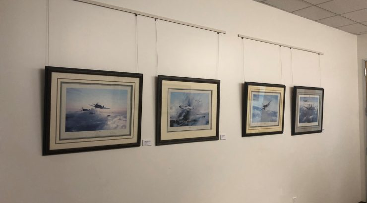 Four lithographs of aircraft hanging on a white wall.