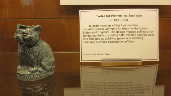 A small cat statue displayed next to explanatory text