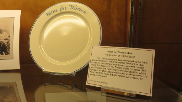 """A white plate with the words """"Votes for Women"""" in blue displayed next to explanatory text"""