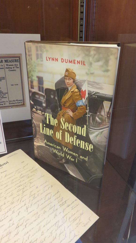 """The book """"The Second Line of Defense"""" standing in a display case next to other memorabilia"""